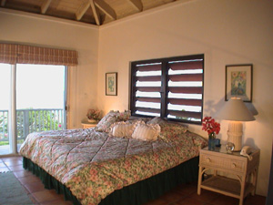 St John rental home Altamira bedroom with high ceilings, king sized bed and sliding glass door onto patio with views