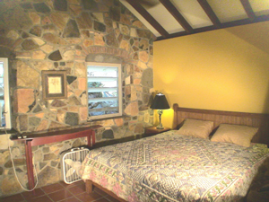 St John cottage Cactus Flower bedroom has stone walls, high ceiling and king sized bed and even a stone shower